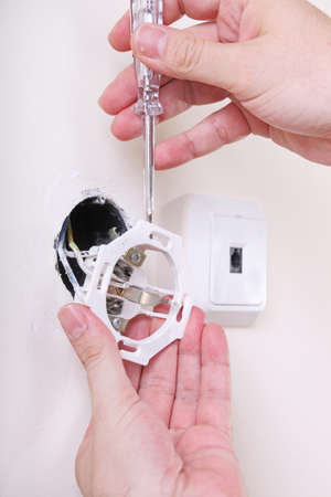 wall socket: man is repairing a wall socket