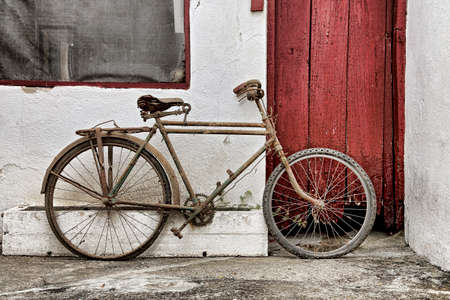 vintage bicycle against old building with wooden door photo