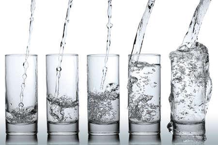 Stadien der gießt Wasser in ein Glas Standard-Bild