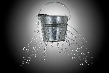 water is coming out of a bucket with holes photo