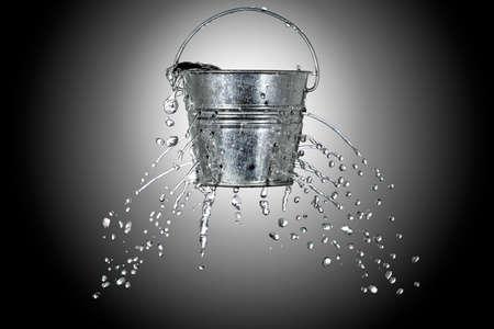 water komt uit een emmer met gaten Stockfoto