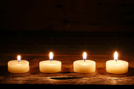 candle lights: four burning candles on wood
