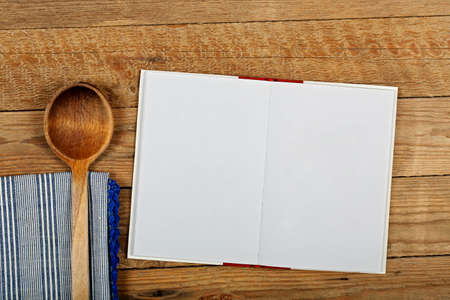 books on a wooden surface: open cookbook with blank pages for backgrounds