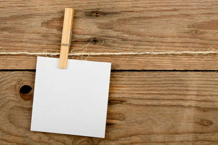 post it note: post it note with clothes peg against wooden surface Stock Photo