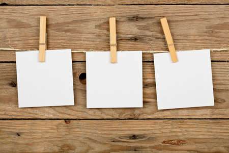 three post-it notes hung with wooden clothes pegs Stock Photo