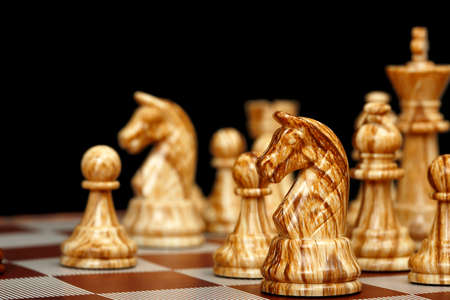 closeup of chess pieces on chessboard on black background photo