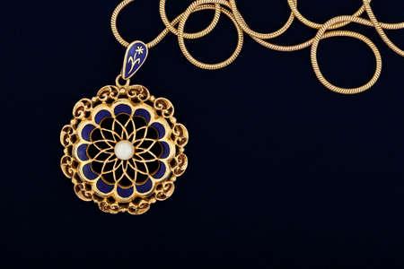 macro of antique gold pendant on dark blue felt texture photo