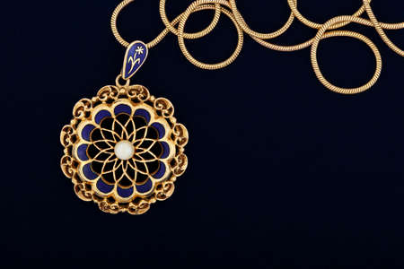 macro of antique gold pendant on dark blue felt texture photo