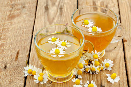 chamomile tea with chamomile flowers on wood