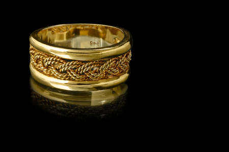 elaborate: elaborate gold ring on black background