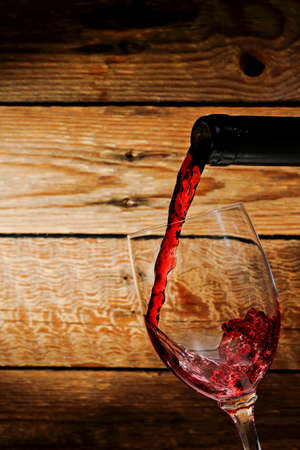 wine being poured into glass against wooden background photo