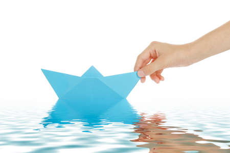boys hand with paper boat on water surface photo