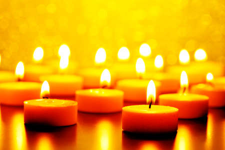 many burning candles against yellow bokeh background