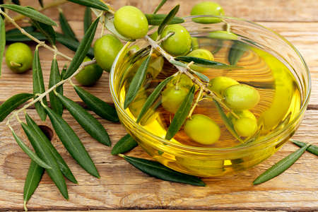olive: olive tree branch dipped in bowl of olive oil Stock Photo