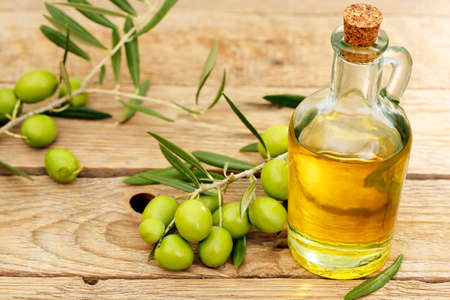 olive oil with branch of olive tree placed on wooden background Imagens