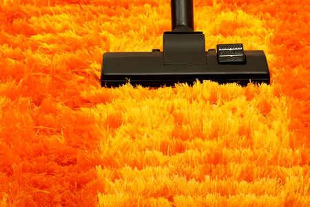 fluffy: vacuum cleaner on orange fluffy carpet closeup