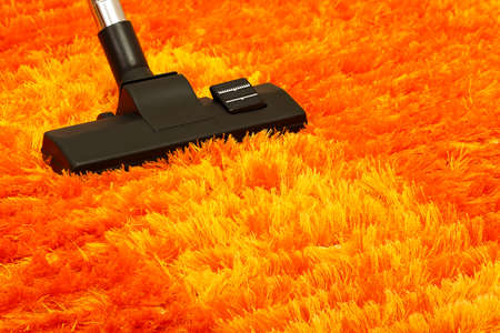 vacuum cleaner: vacuum cleaner on orange fluffy carpet closeup