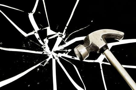 destroying: hammer on a black cracked glass