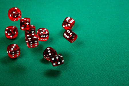 red dice: tossing transparent red dice over green felt