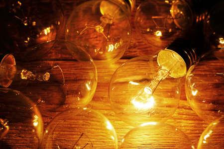unlit: lit light bulb among unlit ones on wood Stock Photo