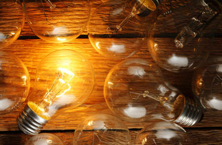 think different: lit light bulb among unlit ones on wood Stock Photo