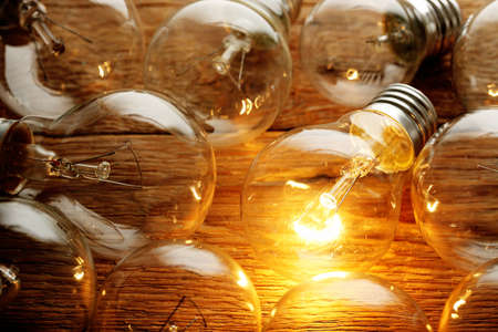 lit light bulb among unlit ones on wood Stock Photo