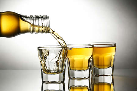 shot glasses: pouring whiskey into shot glasses