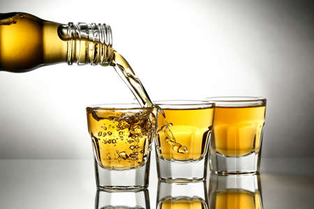 pouring whiskey into shot glasses