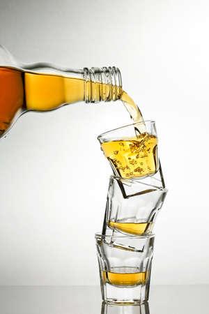 shot glasses: pouring whiskey into shot glasses
