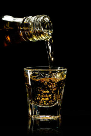 bourbon: pouring whiskey into a shot glass against black