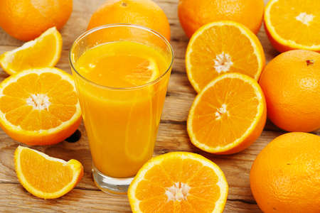 juice glass: glass of orange juice with oranges on wooden surface