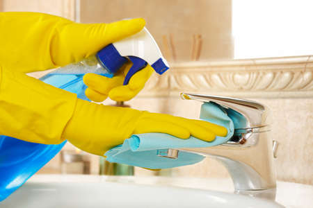 woman in rubber gloves with rag and detergent cleaning the bathroom photo