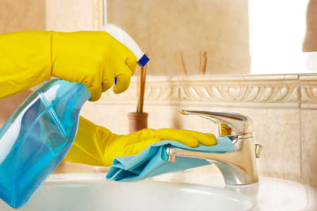 woman in rubber gloves with rag and detergent cleaning the bathroom