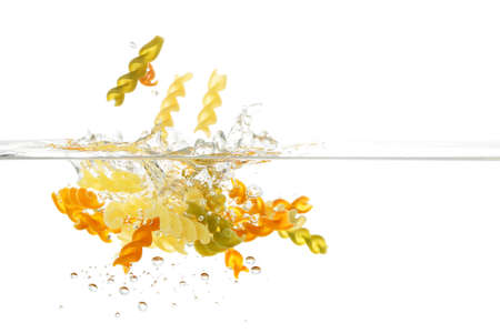 fusilli pasta being dropped into water Stock Photo