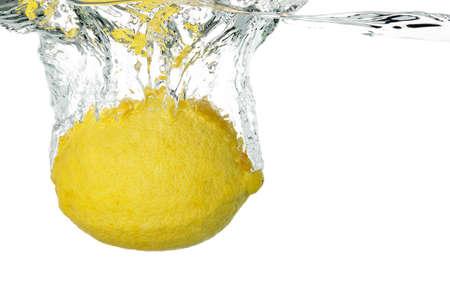 lemon sinking into water on white