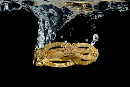 elaborate: elaborate gold bracelet splashing in water against black