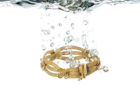 elaborate: elaborate gold bracelet splashing in water Stock Photo