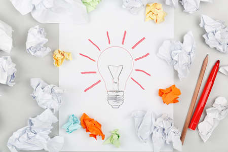drawn lightbulb surrounded by crumpled pieces of paper photo