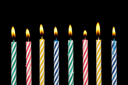 eight colorful birthday candles with flame on black Reklamní fotografie