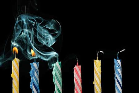 gateau anniversaire: bougies d'anniversaire qui viennent d'être soufflées avec de la fumée sur fond noir Banque d'images