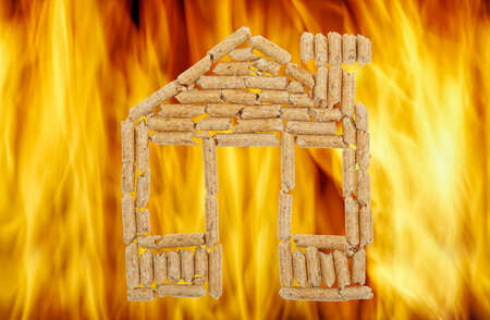 wood pellets: wood pellets in the shape of a house against vibrant flames
