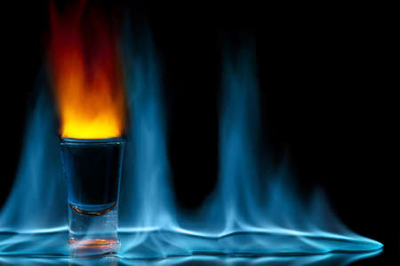 shot glass on fire against black background photo