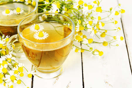 chamomile tea: cup of chamomile tea with chamomile flowers on wooden planks