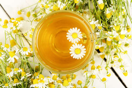 chamomile tea: cup of chamomile tea with chamomile flowers on white wooden planks Stock Photo