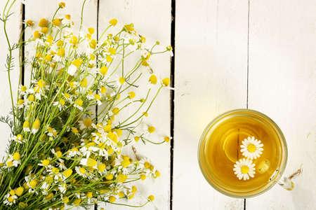 흰색 나무 널빤지에 카모마일 꽃과 카모마일 차 한잔
