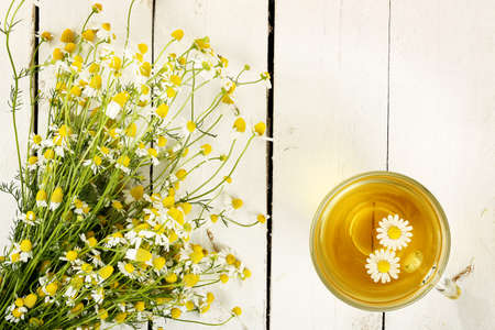 cup of chamomile tea with chamomile flowers on white wooden planks Banque d'images