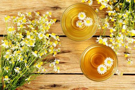 木製の板にカモミールの花とカモミール茶のカップ