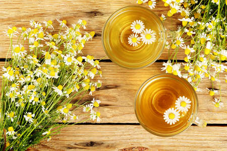 cups of chamomile tea with chamomile flowers on wooden planks Standard-Bild