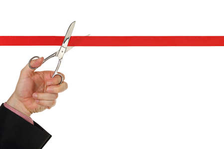 hand with scissors cutting a red ribbon isolated on white photo