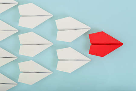 mision: avi�n de papel de color rojo que lleva las blancas, concepto de liderazgo Foto de archivo